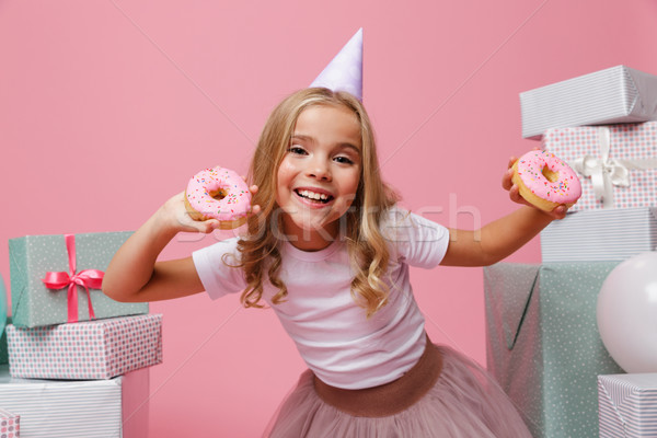 Portrait of a cheery little girl in a birthday hat Stock photo © deandrobot