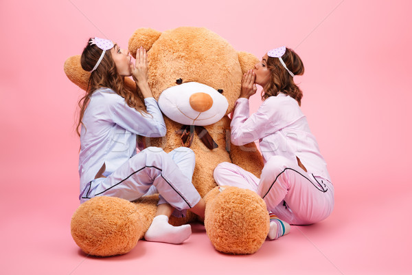 Two girls dressed in pajamas sitting with a big teddy bear Stock photo © deandrobot