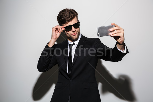 Playful macho in black classic suit and sunglasses taking selfie Stock photo © deandrobot