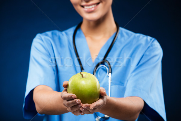 Doctor swith stethoscope holding and showing green apple Stock photo © deandrobot