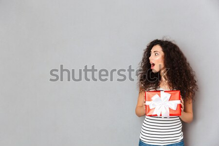 Pleased female covering her face with festive box gift-wrapped b Stock photo © deandrobot