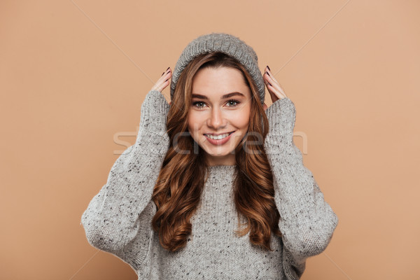 Young attractive brunette woman straightening her hat while look Stock photo © deandrobot