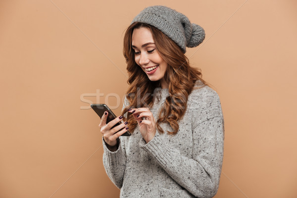 Young smiling brunette woman in woolen hat and sweater typing me Stock photo © deandrobot
