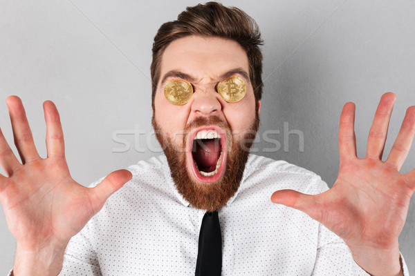 Close up of an excited businessman with bitcoins Stock photo © deandrobot