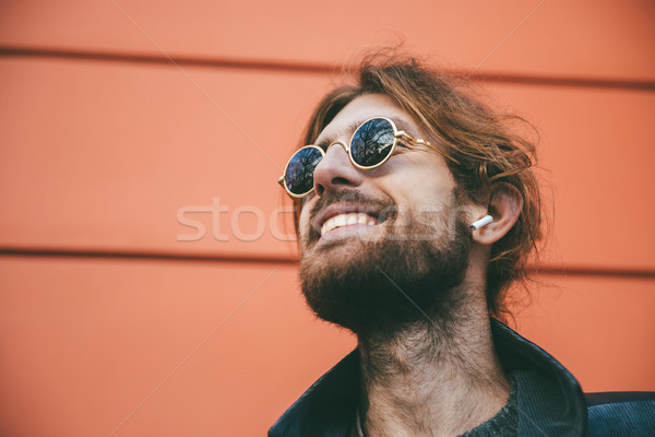 Close up portrait of a happy bearded man in earphones Stock photo © deandrobot