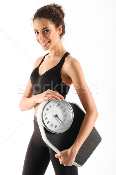 Vertical image of a happy curly brunette fitness woman Stock photo © deandrobot