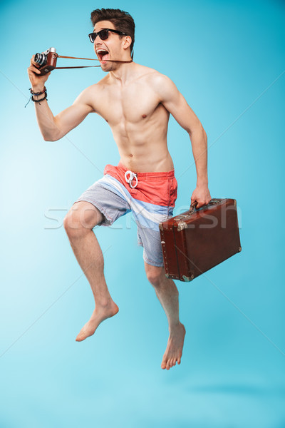 Full length portrait of a cheerful young shirtless man Stock photo © deandrobot