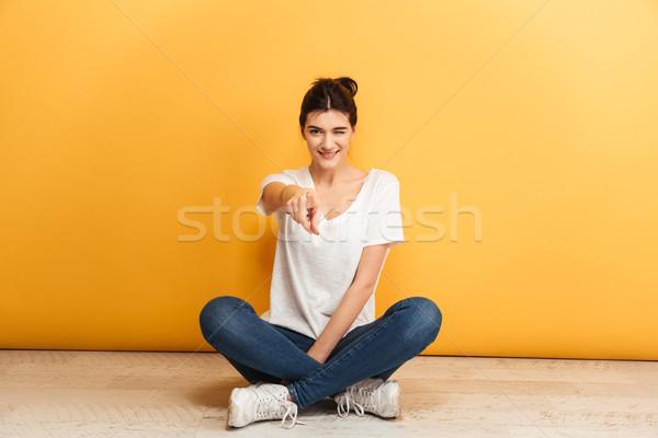 Portrait souriant jeune femme séance jambes croisées étage Photo stock © deandrobot