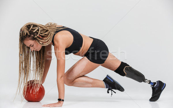 Disabled sportswoman isolated make exercises with ball. Stock photo © deandrobot