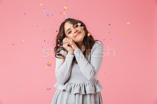 Pleased brunette woman in dress posing with arms together Stock photo © deandrobot