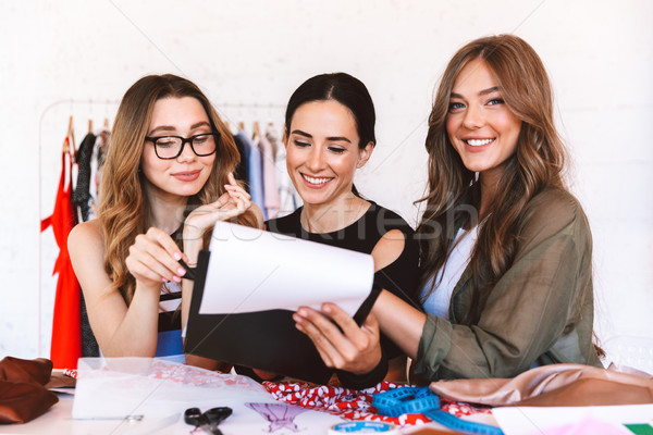 Three cheerful young women clothes designers Stock photo © deandrobot