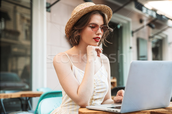 Pretty woman in dress and straw hat using laptop computer Stock photo © deandrobot