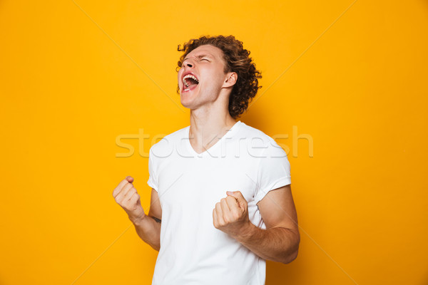 Photo of happy man 20s in casual t-shirt rejoicing and screaming Stock photo © deandrobot