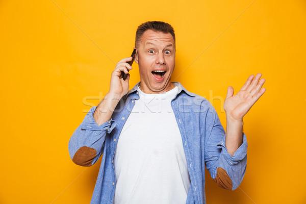 Portré örömteli középkorú férfi beszél mobiltelefon izolált Stock fotó © deandrobot