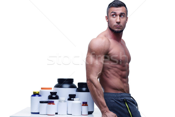 Muscular man leaning on the table with sports nutrition Stock photo © deandrobot