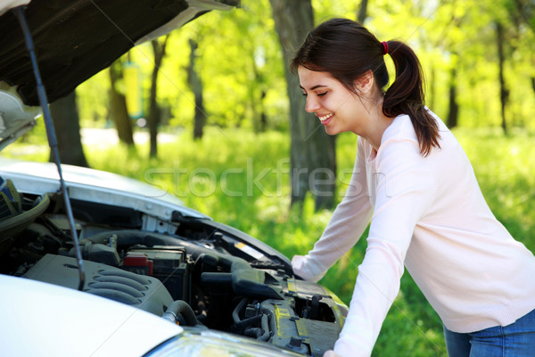 Happy woman looks under hood car background green park Stock photo © deandrobot