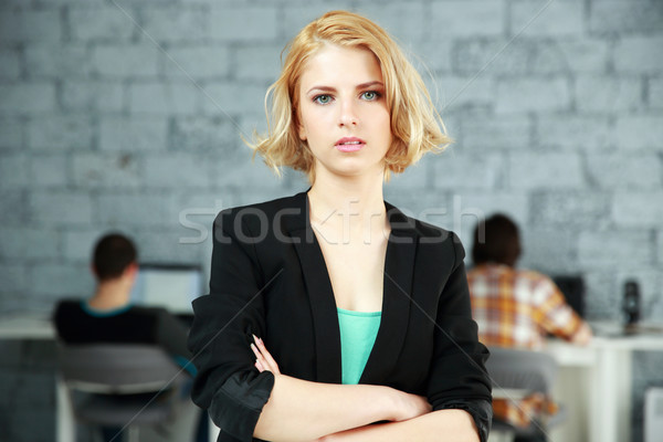 Portrait of a young pensive woman standing with arms folded in office Stock photo © deandrobot
