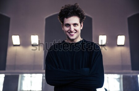 Smiling businessman with arms folded standing on gray background Stock photo © deandrobot