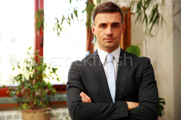 Confident businessman standing with arms folded at office Stock photo © deandrobot
