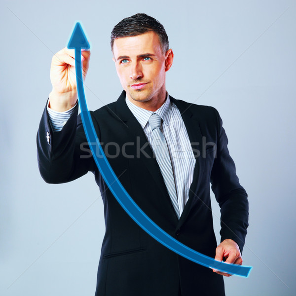 Businessman drawing a rising arrow, representing business growth. Stock photo © deandrobot