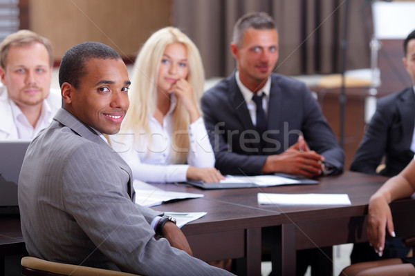 Happy african-american businessman with his team working behind Stock photo © deandrobot