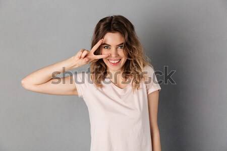 Happy cute woman combing her hair Stock photo © deandrobot