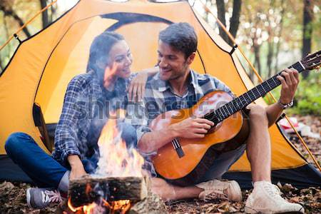 Couple sitting with guitar near bonfire  Stock photo © deandrobot