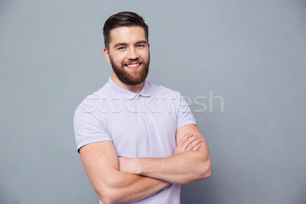 Happy man standing with arms folded Stock photo © deandrobot