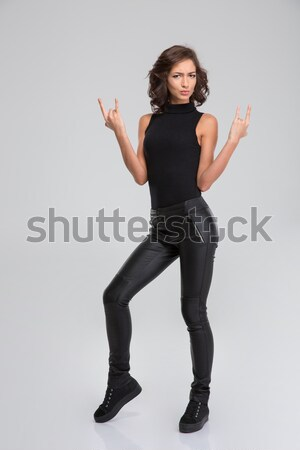 Serious young female showing rock and roll sigh Stock photo © deandrobot