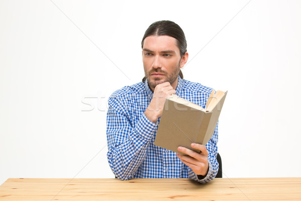 Thoughtful handsome student with long hair sitting and reading Stock photo © deandrobot
