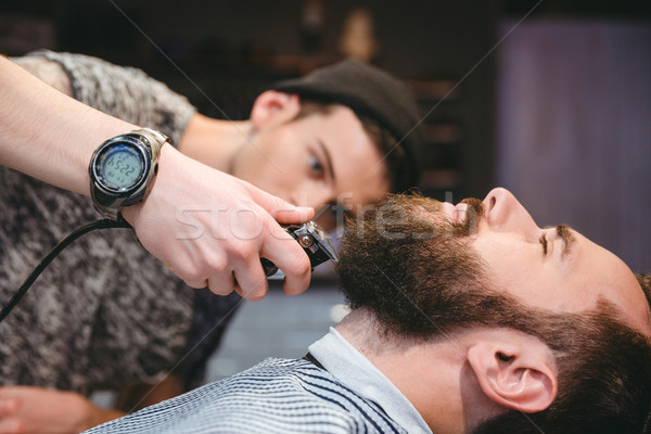 Bearded man getting his beard shaved by modern barber  Stock photo © deandrobot
