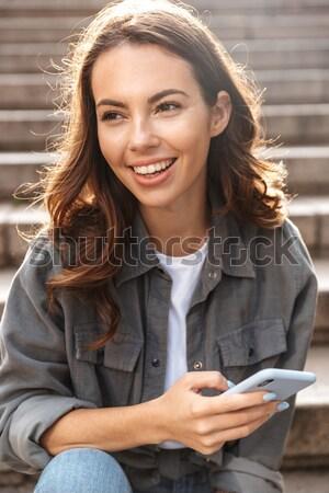 Gyönyörű lány hosszú vörös haj okostelefon portré boldog Stock fotó © deandrobot