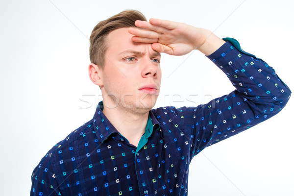 Amusing concentrated man looking far away with hand above eyes  Stock photo © deandrobot