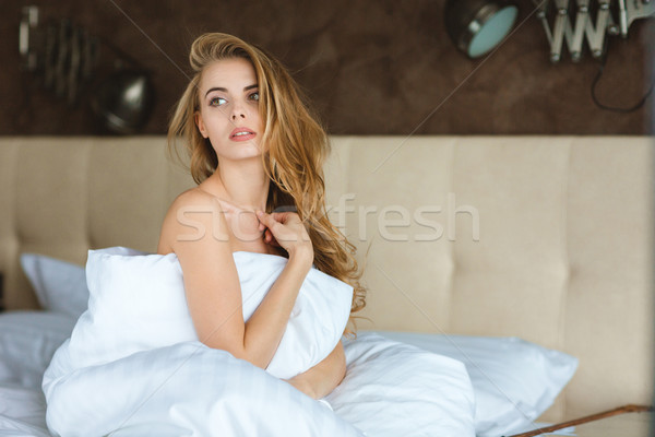 Attractive relaxed young woman sitting on bed Stock photo © deandrobot