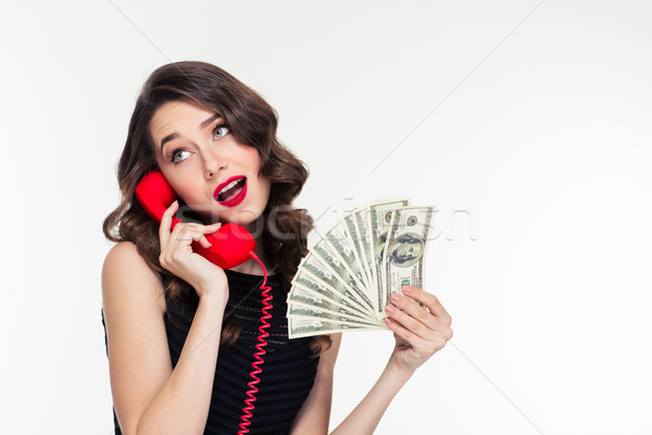 Attractive joyful curly female holding money and talking on telephone Stock photo © deandrobot