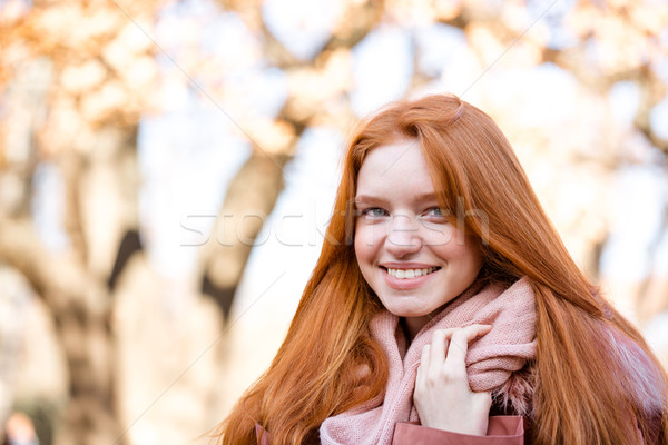 Smiling redhead woman looking at camera outdoors Stock photo © deandrobot