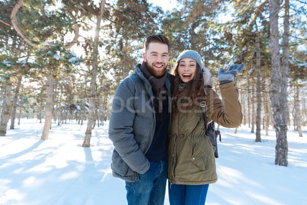 Laughing couple standing in winter park Stock photo © deandrobot