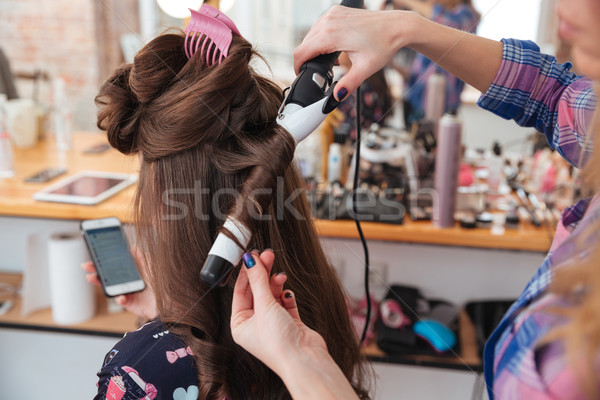 Hairdresser using curling iron for hair of female with smartphone Stock photo © deandrobot