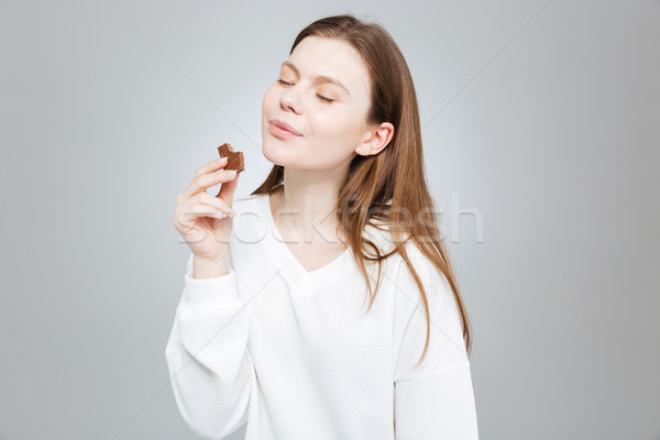 Lovely smiling teenage girl with eyes closed eating chocolate  Stock photo © deandrobot