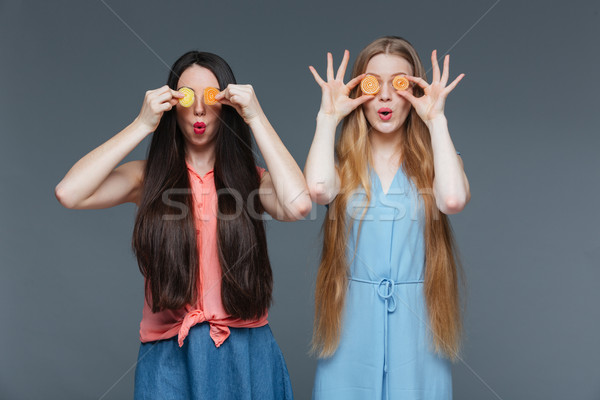 Two funny amazed women covered their eyes with marmalade candies  Stock photo © deandrobot
