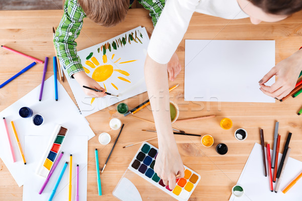 Little son and mother painting with watercolor paints on table Stock photo © deandrobot