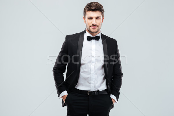Confident young man in tuxedo with bowtie Stock photo © deandrobot