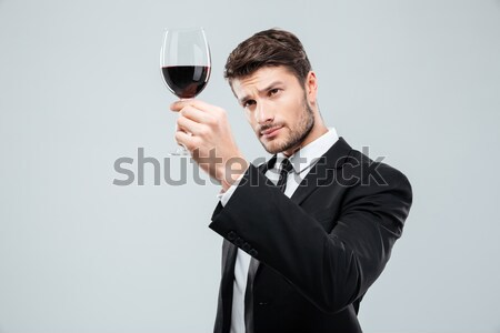 Focused young male sommelier looking at red wine in glass Stock photo © deandrobot