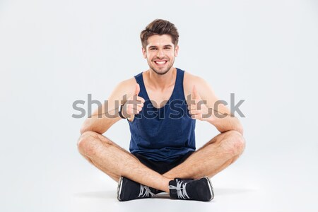 Cheerful sportsman sitting with legs crossed and pointing on you Stock photo © deandrobot