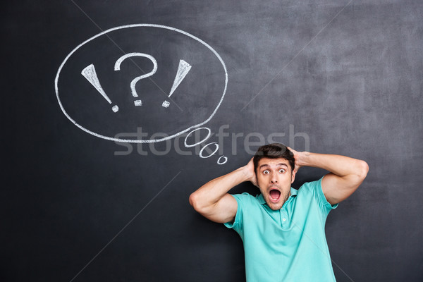 Shocked astonished man over chalkboard background with speech bubble Stock photo © deandrobot