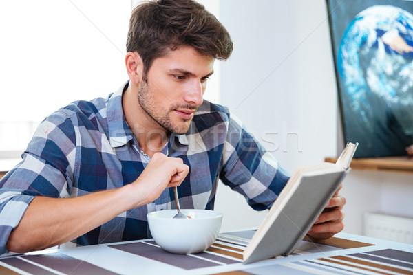 Man lezing boek eten granen melk Stockfoto © deandrobot