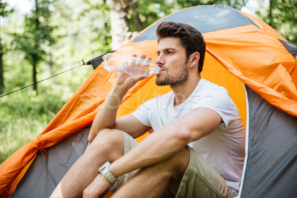 Man sitting near touristic tent and drinking water in forest Stock photo © deandrobot