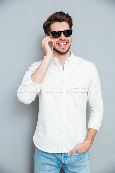 Stockfoto: Glimlachend · knap · jonge · man · zonnebril · praten · mobiele · telefoon
