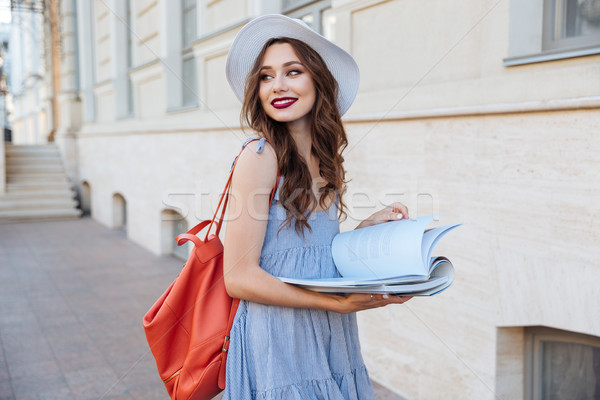 Happy pretty young woman reading a book on the street Stock photo © deandrobot