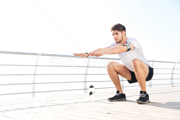 Young handsome sportsman doing squatting outside at the pier Stock photo © deandrobot